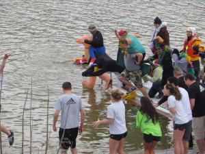 Frosty frolickers plunge into the icy waters of the Monongahela River