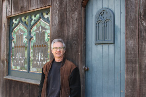 Vince Gillen poses outside of his studio
