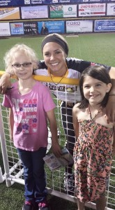 Raelyn Hersberger and Arabella Martin pose for a photo with a player after the home opener on May 29. Fans are invited to visit the field after every game to meet the players and get their autographs free of charge.