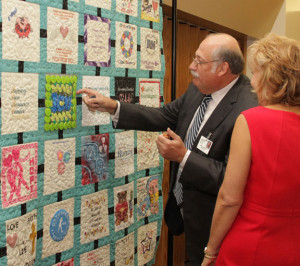 Monongahela Valley Hospital President and CEO Louis J. Panza Jr. examines the Intensive Care Unit quilt square that incorporated colorful medicine bottle caps. The quilt will be on display in the hospital lobby.
