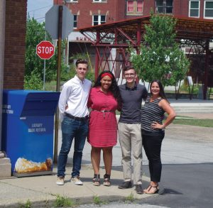 Students in Action members Jakob Sabatula (left), Jayda Smith, and Andrew Haven, along with sponsor Kellie Polvinale, gather outside the Brownsville Free Public Library, where the team is creating a teen space.